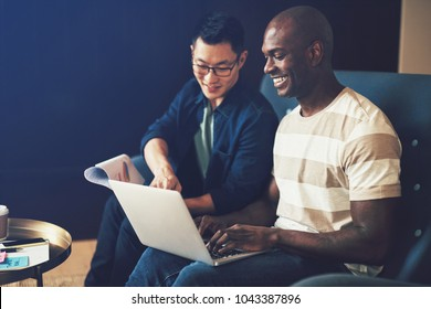 Two diverse work colleagues sitting together on a sofa in an office laughing while working on a laptop and discussing paperwork