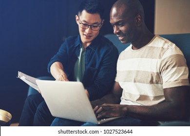 Two diverse work colleagues smiling while sitting together on a sofa in an office discussing paperwork and working on a laptop