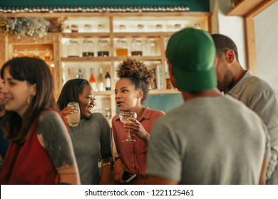 Two diverse young female friends talking together over cocktails while standing with friends in a bar