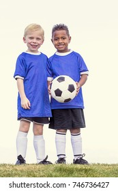 Two diverse young soccer players holding a soccer ball