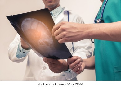 Two Doctor examining x-ray film of patient on background look old or vintage style. (vintage color tone)