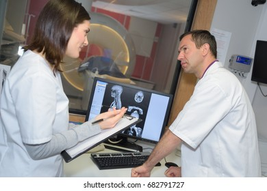 two doctor examining x-ray film of patient
