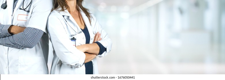 Two doctors arms crossed in a hospital corridor, blurred background