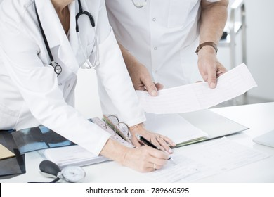 Two doctors consulting patient's ECG and x-ray results at the office