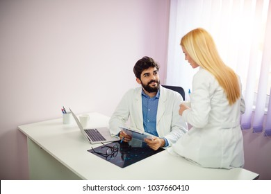 Two doctors discussing about patient report in ward at hospital.