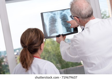 Two doctors examining x-ray report in medical office