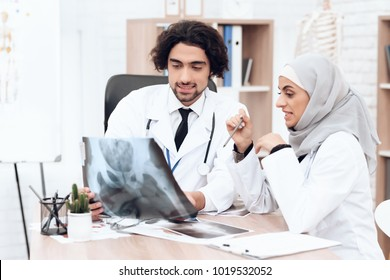Two doctors are examining an x-ray of a sick patient. A woman wears a hijab. Arabian hospital concept.
