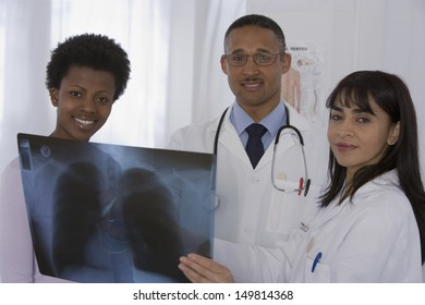 Two doctors and patient looking at x-ray