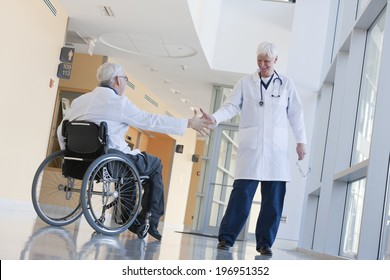 Two doctors shaking hands in hospital corridor, one with spinal cord injury and in a wheelchair