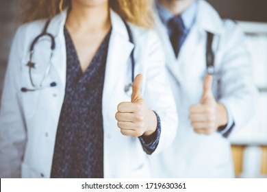 Two doctors standing with thumbs up in hospital office. Medical help, countering viral infection and medicine concept