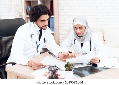 Two doctors are studying the patient's documents. A woman wears a hijab.