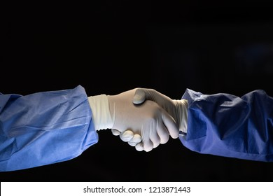 Two doctors in surgery cloth with rubber gloves shaking hands with team confident before start to do cure operation in dark surgery room.
