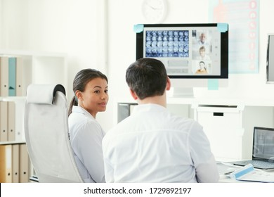 Two doctors talking to each other while sitting at the table and examining x-ray images at office