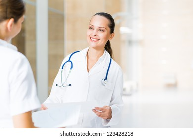 two doctors talking in the lobby of the hospital,