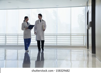 Two doctors walking and smiling in the hospital