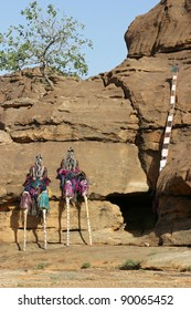 Two Dogon dancers on stilts are taking a break. On the right side, just behind a rock is a dancer with a so-called tall mask (sometimes more than 10 feet).