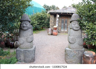 Two Dol Hareubang statue with hat and hands on belly at Jeju island, South Korea