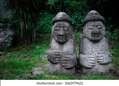 Two Dol Hareubang statues with hats and hands on belly in dark green forest, Seogwipo, Jeju Island, South Korea