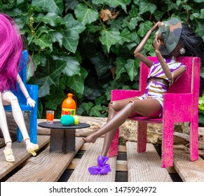 Two doll friends sitting on an outdoor terrace drinking lemonade. Handmade cardboard furniture painted pink and blue. One black skin woman doll and a white skin woman doll. Wearing shorts and sandals.