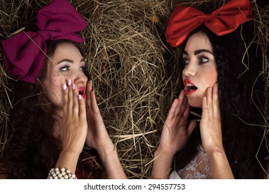 two doll women gossiping on the background of hay
