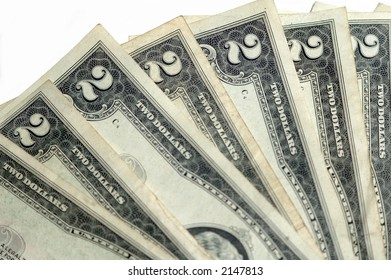 two dollar bills fanned closeup on a white background