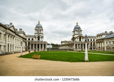 The two domed towers of the Old Royal Naval College, Greenwich, London, England frame a cloud on a spring day. London - UK, April 7, 2017