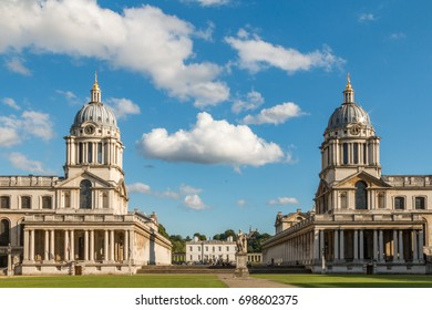 The two domed towers of the Old Royal Naval College, Greenwich, London, England frame a cloud on a summer day