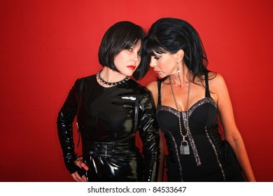 Two dominatrix women pose invitingly on a red background.