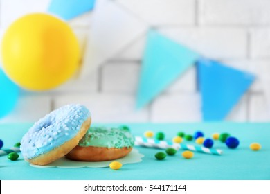 Two donuts and Birthday decor on blurred brick wall background