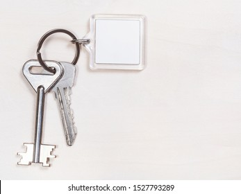 two door keys on keyring with blank white keychain on pale brown table