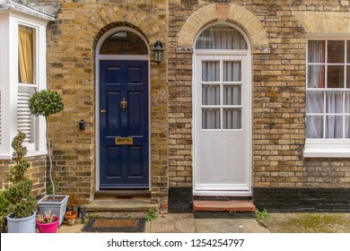 Two doors from different houses in a brick wall, in the streets of an English village