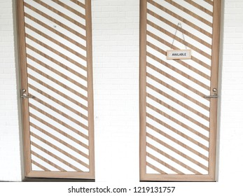 Two doors with white striped pattern in wooden board and white brick wall