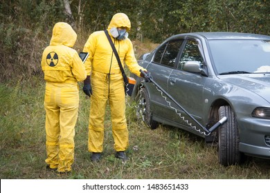 Two dosimetrist  in protective suite and mask with geiger counter measuring radiation level on car