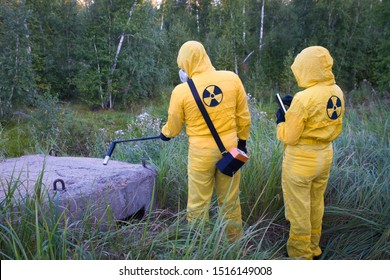 Two dosimetrist  in protective suite and mask with geiger counter measuring radiation level in danger zone