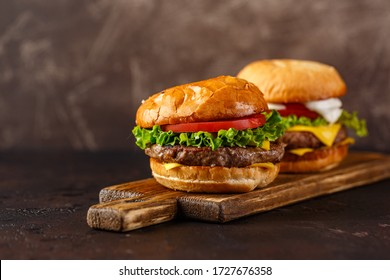 Two double cheeseburger with lettuce, tomato and melted cheese on wooden board