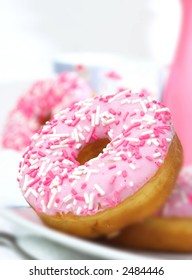 Two doughnuts with pink icing and sprinkles