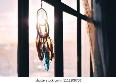 Two dream catchers hanging on the window at sunset time. Boho chic, hope freedom and dream concept.
