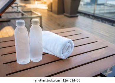 Two drinking bottle of water with white towel on wooden table near swimming pool.