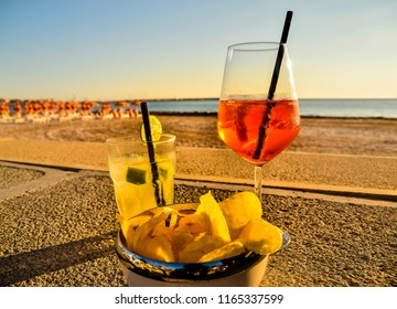 Two drinks and snack on a sunset in front of a beach