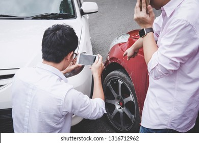 Two drivers man arguing after a car traffic accident collision and making phone call to Insurance Agent and take a photo, Traffic Accident and insurance concept.