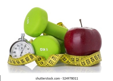 Two dumbbells, red apple, measuring tape isolated on white background. Diet concept.