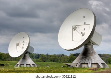 Two earth station satellite installations  - the type used for broadcasting. Poor weather.