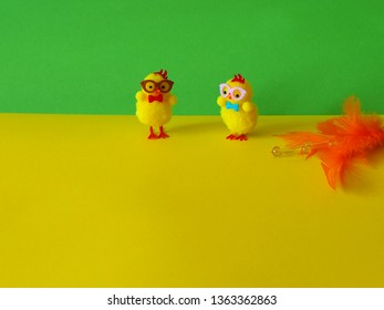 Two Easter chickens with orange decoration on yellow and green background, space for text