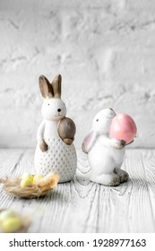 Two Easter porcelain rabbits stand on a white wooden table. In the paws rabbits hold Easter eggs. In theticipation of the Easter holiday, a composition