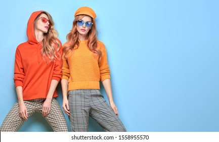 Two easy-going happy hipster Woman smiling, Stylish fashion orange colored outfit. Beautiful Girl in Trendy sunglasses, sweatshirt, cap. Joyful sister, friend. Creative fashionable friendship concept