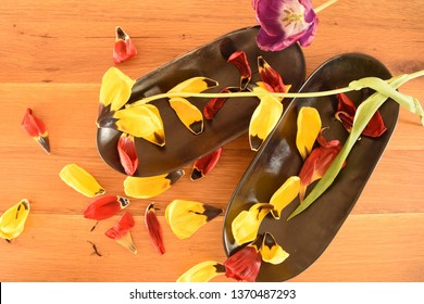 Two ebony bowls with petals of red and yellow tulips, green branch and open tulip lilac fallen on top, inside and outside.