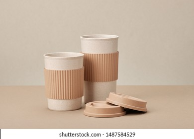 Two Eco Coffee Cup Isolated on Beige Background Closeup Copy Space Photo. Stylish Paper Container Different Size for Morning Hot Energy Drink. Disposable Eco-friendly Cardboard Mugs for Beverages