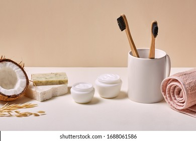 Two eco-friendly bamboo toothbrushes in cup facial cream in jar organic coconut soap and towel isolated in bathroom close-up