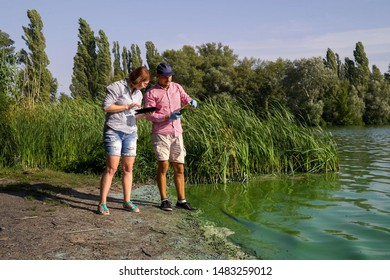 two ecologists take sample of green algae on river bank and enter data on tablet