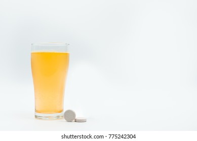 Two effervescent tablets on white background and orange effervescent bubbles of calcium and vitamin C effervescent tablets in transparent glass. Vitamins, minerals and supplement concept.